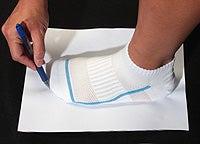Човек, проследяващ контура на крака си върху бял лист хартия