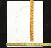 2 линейки се използват за измерване на дължината и ширината на очертанията на крака, проследени върху хартия